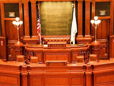 photo of a empty courtroom, all wood desk and partition with two flags on both sides of the judge's seat - one the American flag